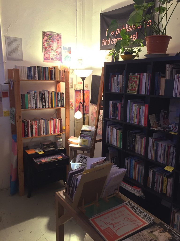 photo of library space, shows shelves of books, with plants, and posters and banners on the walls