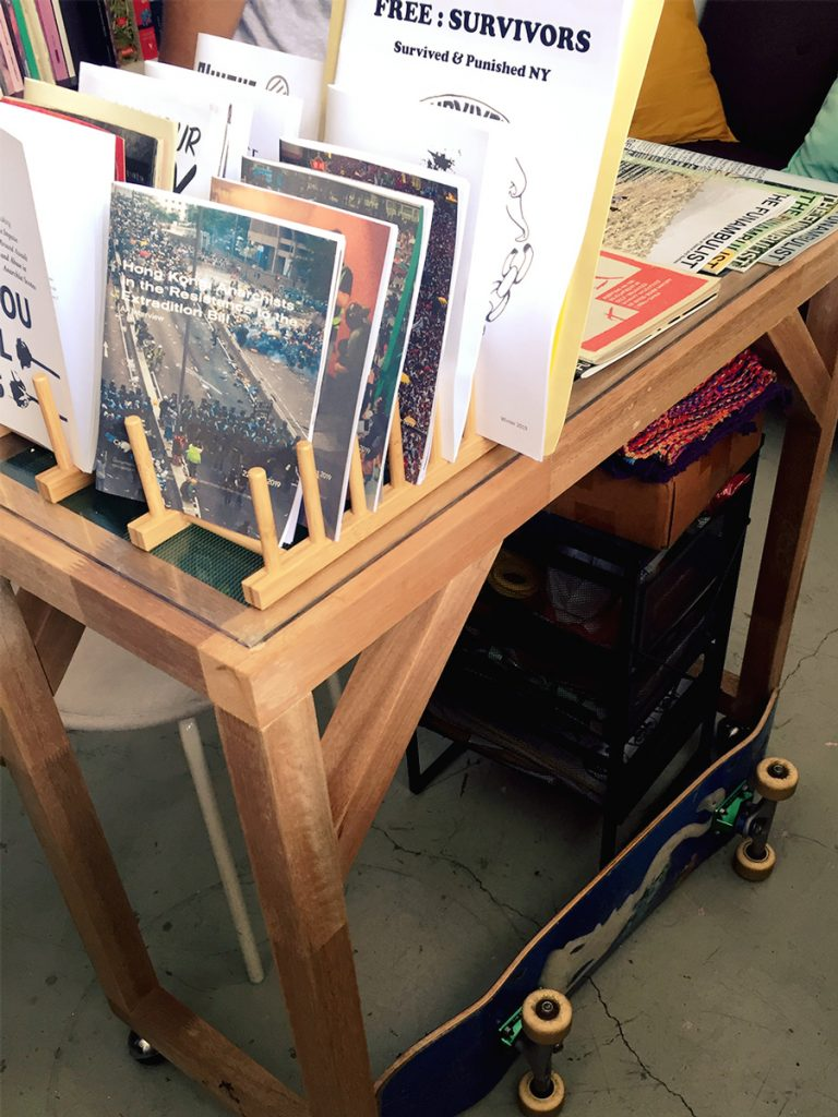 photograph of a display table in the library, zines and magazines can be seen on it, and a skateboard sits on the floor beside
